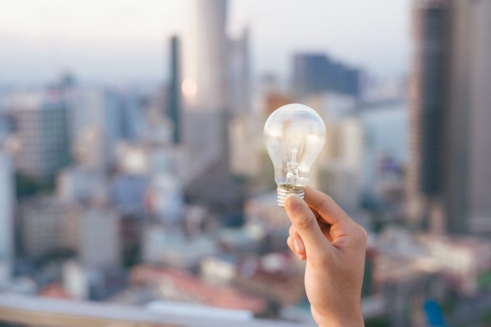 Person holding lightbulb in front of city skyline