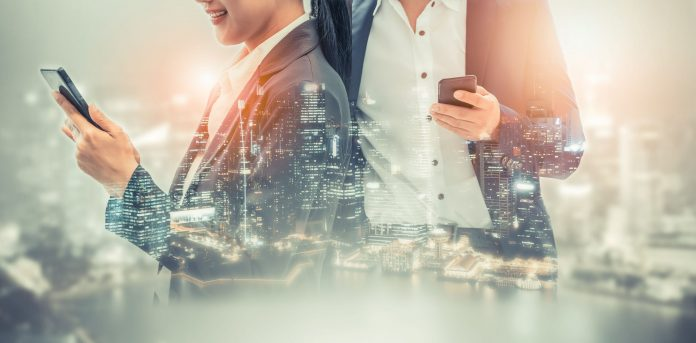 professional man and woman holding cell phone skyline background