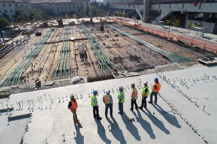 Construction workers standing over a site talking