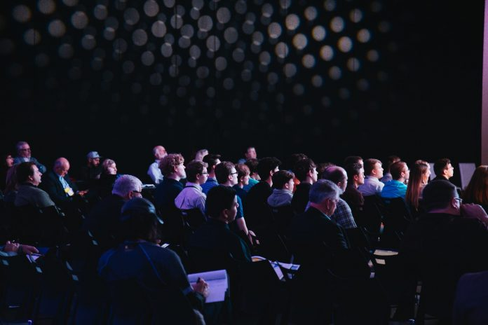 crowd of people taking notes at conference