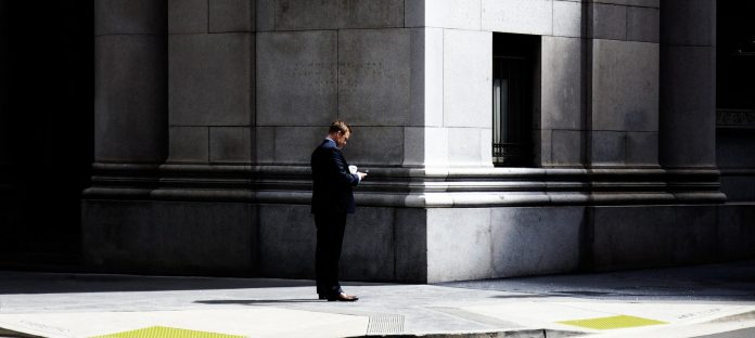 man standing outside bank on phone