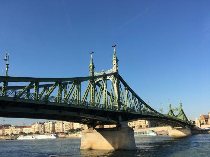 green bridge over river in city