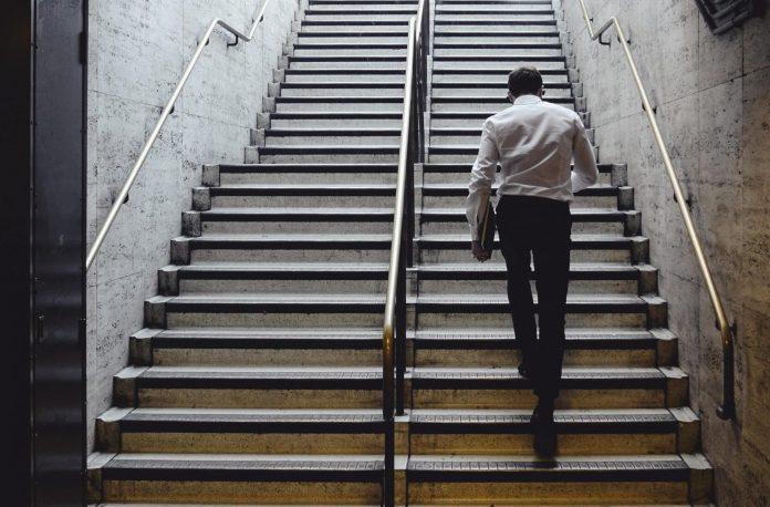 man walking upstairs in office building