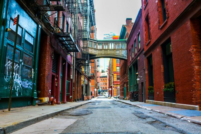 Red brick alleyway with bridge walkway