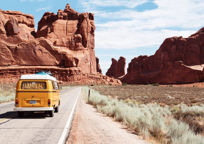 VW bus driving in Arizona desert with canyons