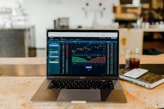 laptop on desk showing graph of stock market activity