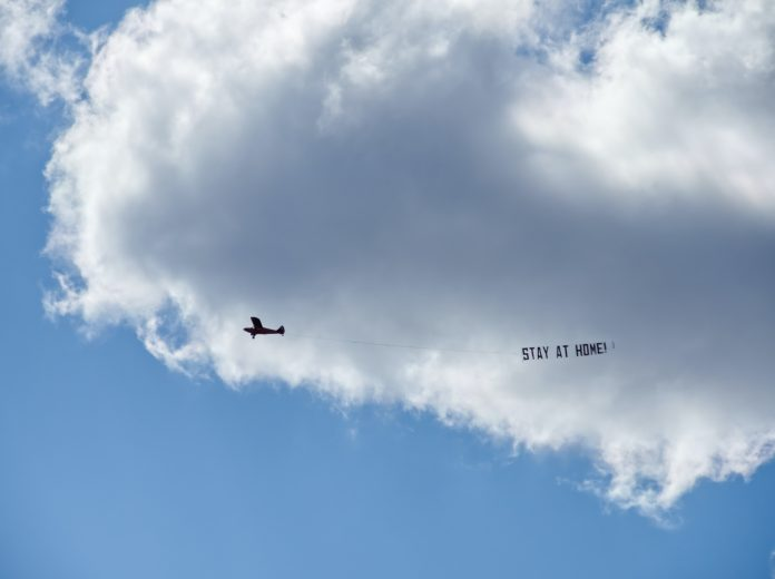 plane flying against cloud with sign saying stay at home