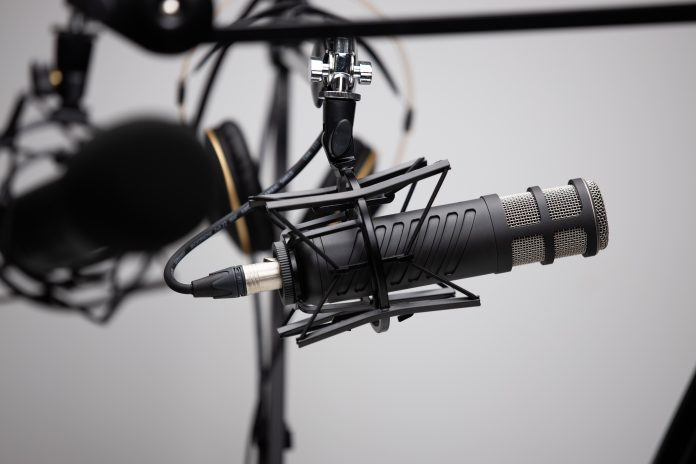 studio microphone on stand with headphones and gray background