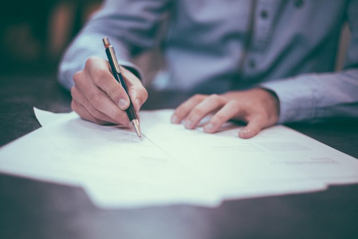 man in business wear signing contract
