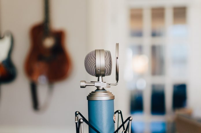 blue bottle microphone against a yellow wall with guitars hanging on it