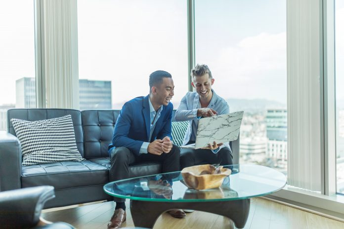 two men in office skyriser looking at laptop